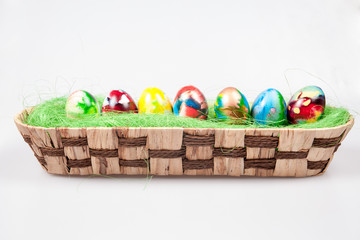 Colorful Easter eggs in wicked pannier on a white background