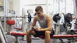 young man with smartphone in gym