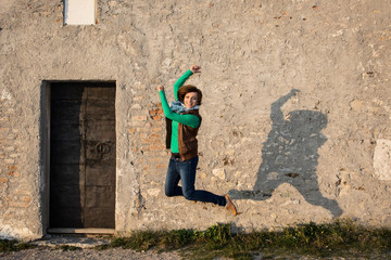 Young woman is jumping for joy in front of the old wall