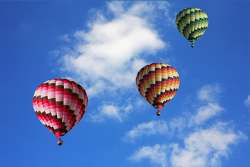 Three big multi-colored balloons in the blue sky