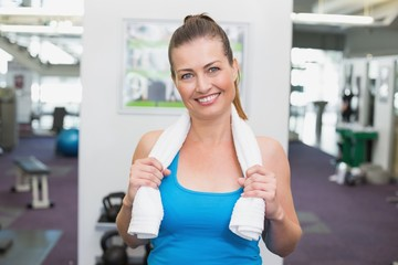 Fit brunette smiling at camera in fitness studio
