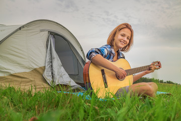 Teenage  girl near the tent playing a guitar