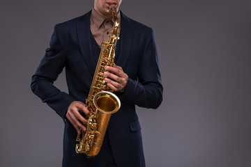 Close-up picture of a trumpet in hands of a jazz man in a suit i