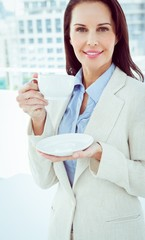 Smiling businesswoman holding a drink