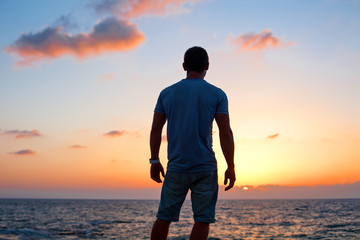 young man silhouette at sunset near the sea
