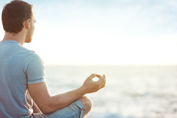 young man in meditation near the sea