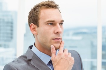 Thoughtful young businessman looking away