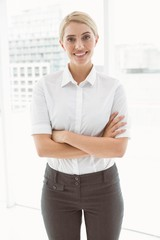 Beautiful businesswoman with arms crossed in office