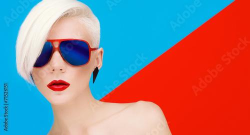 Leinwandbild Motiv Fashion blond model with trendy haircut and sunglasses on bright