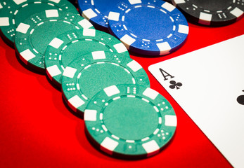 Ace of clubs and chips on a red table