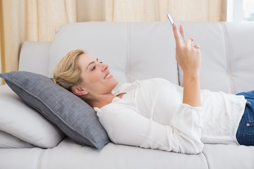 Beautiful blonde using tablet on sofa