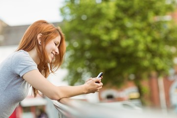 Cheerful redhead with her mobile phone texting a message
