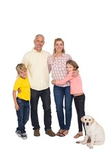 Happy family smiling at camera with pet dog