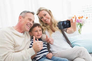 Cheerful family taking self pictures with a smartphone