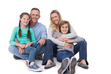 Portrait of a smiling family sitting on the floor