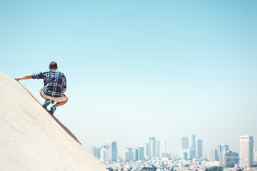 Young man sitting on a cliff and city