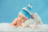 Child in hat hugging toy on a white bedspread, on a blue backgro - Fine Art prints