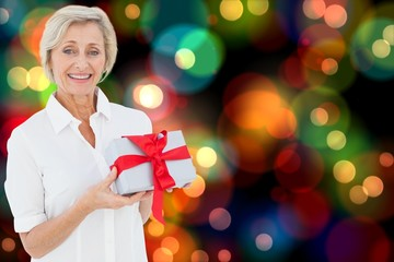Composite image of mature woman holding gift