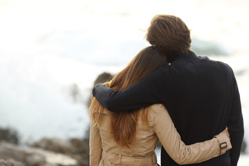 Back view of a couple cuddling in winter