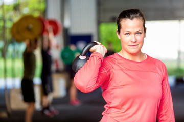 Woman Lifting Kettlebell At Gym