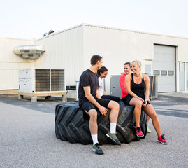 Fit Friends Conversing While Relaxing On Tire