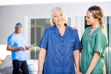 Senior Woman Being Assisted By Female Caretaker In Nursing Home