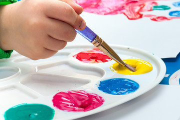 Child painting with brush