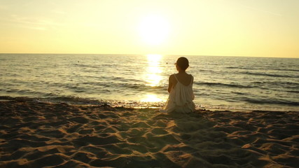 Woman sitting on a sand beach in front of sunset and ocean