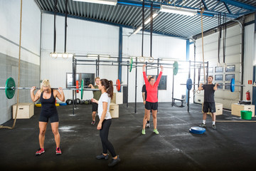 Trainer Assisting Athletes In Lifting Barbells