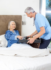 Caretaker Serving Breakfast To Senior Woman On Bed