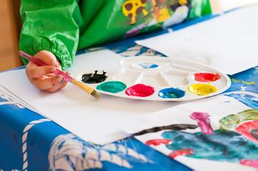 Child painting with brush