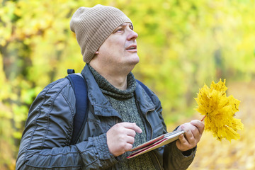 Hiker looking for information in tablet PC in the park