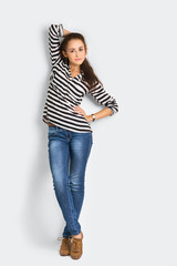 A shot of attractive young casual woman standing at the wall