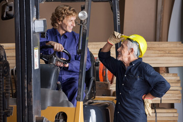 Carpenter Communicating With Colleague Using Forklift