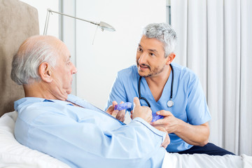 Caretaker Explaining Prescription To Senior Man