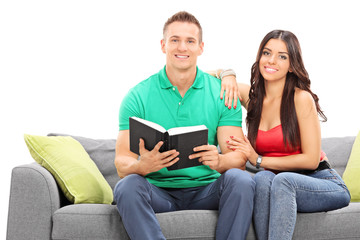 Young couple reading a book seated on sofa