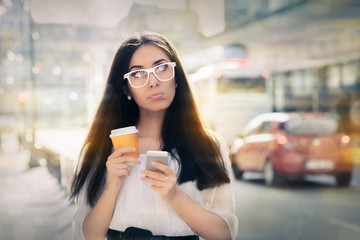 Disappointed Young Woman Holding Smartphone and Coffee Cup