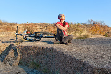Woman sitting on a stone next to mountain bike relaxing and enj