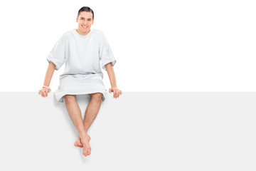 Cheerful male patient sitting on a blank panel
