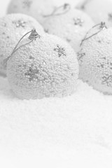Christmas balls on white snowy background