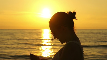 Young woman take a selfie photo by the sea at sunset