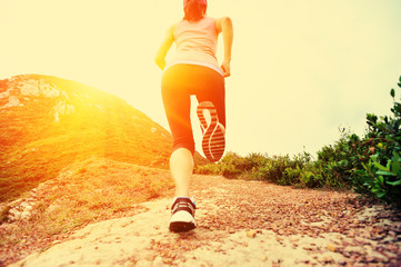 young fitness woman legs running on seaside mountain trail