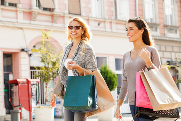 Two beautiful women in shopping. Selective focus on brunette.