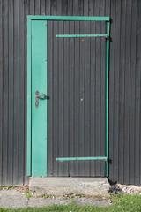 schwarze Türe aus Holz mit grünem Rahmen