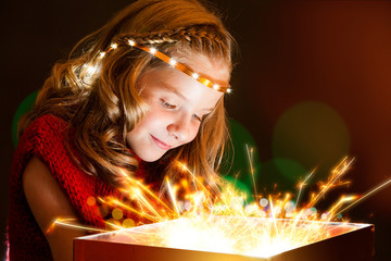 Conceptual portrait of cute girl staring at light box.