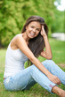 Pretty Smiling Woman Sitting on Grassy Ground