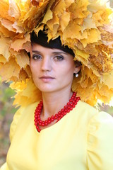 Красивая девушка в осеннем парке в с красными бусами