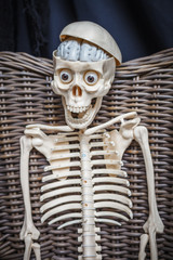 Skeleton sitting in a wicker chair