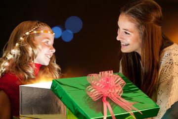 Girls sitting around Christmas presents.