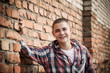 teen boy by brick wall